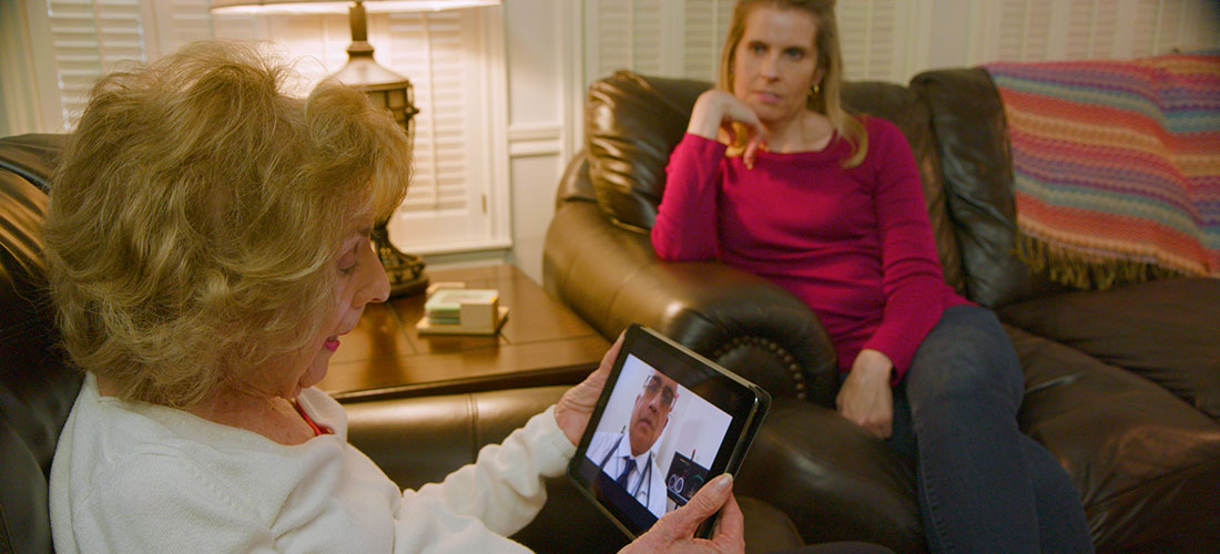 photo of an elderly woman patient receiving telehealth services on a video call with her doctor with adult daughter nearby