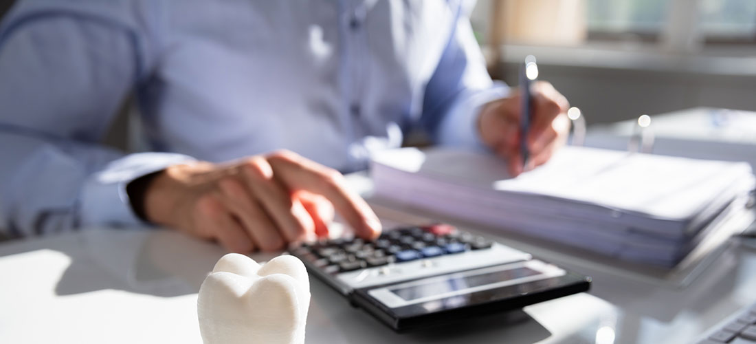 Photo of dentist using calculator and working at desk