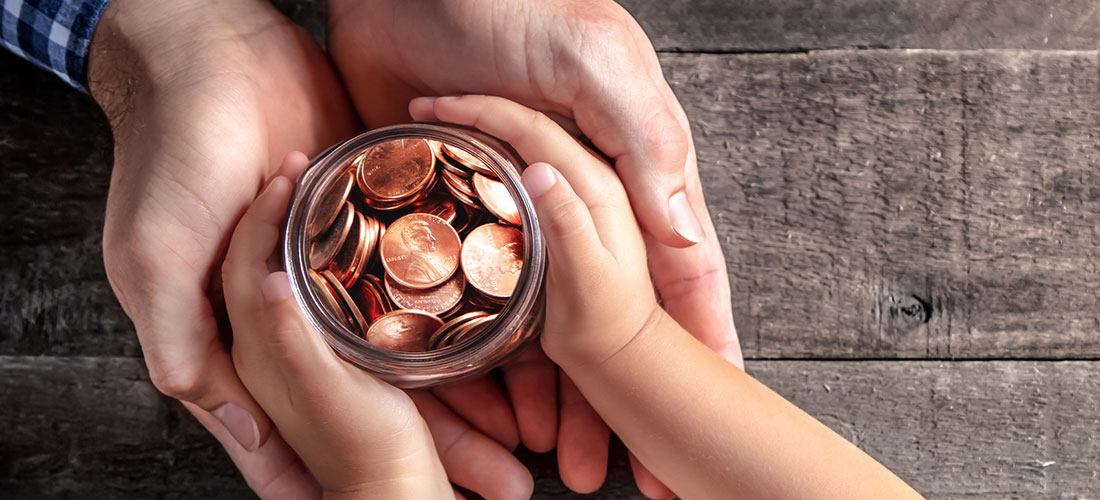 Photo showing the hands of an adult giving a jar of coins to the hands of a child.