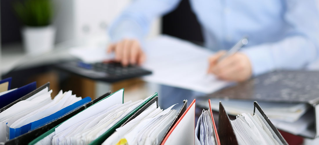 Photo of employee working at desk preparing for the company's first retirement plan audit