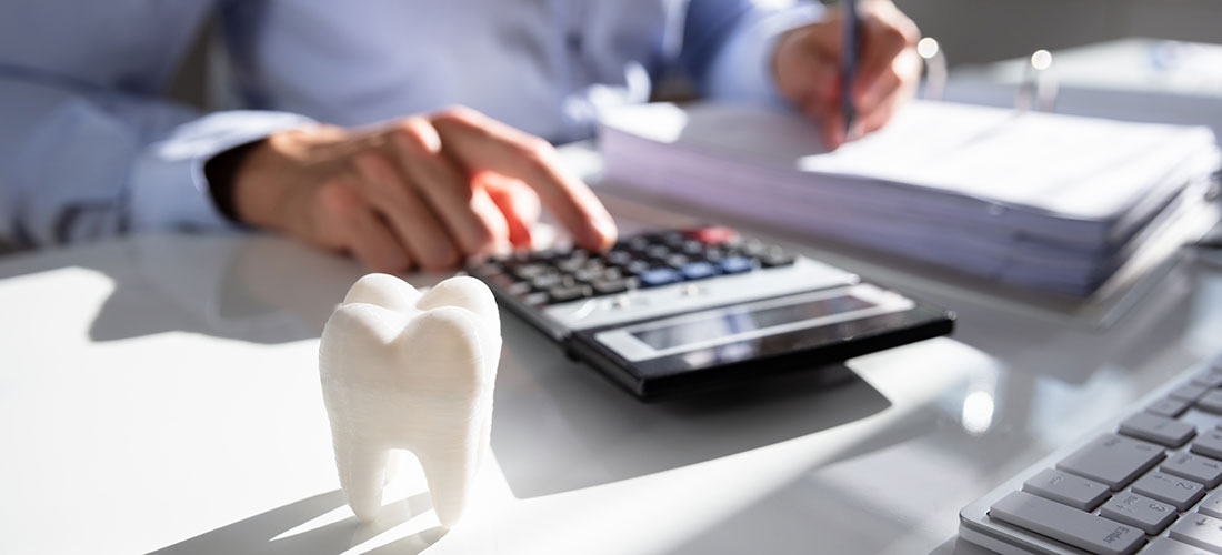 photo of dentist at desk with calculator planning for retirement