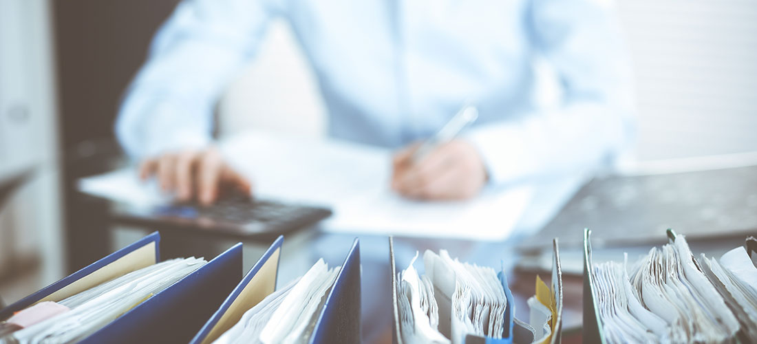Photo of auditor at desk with stacks of papers and calculator