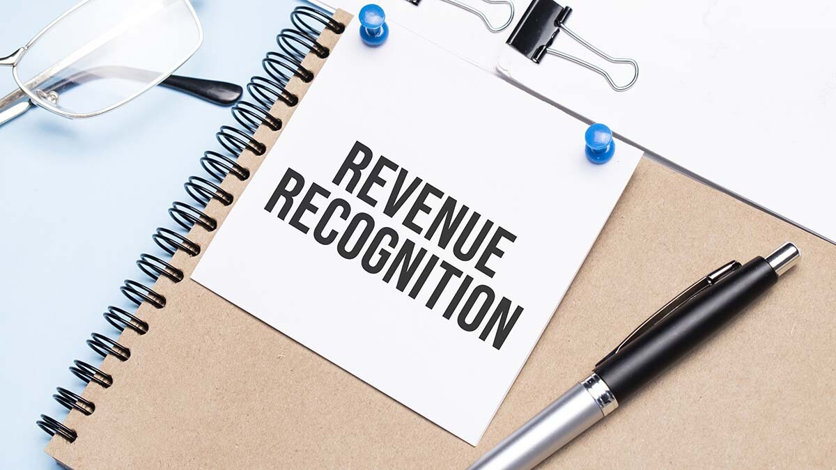 Image of a notebook and a sign that says 'Revenue Recognition'